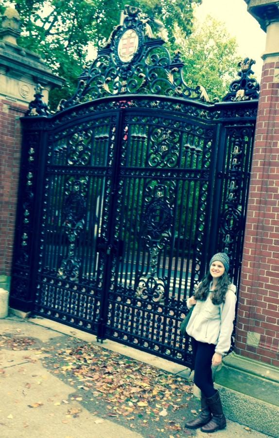 Kate Schneider stands in front of the gate at Brown University.