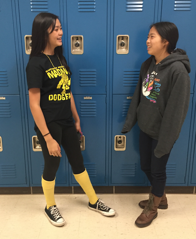 Two+students+happily+converse+with+each+other+in+the+hallway.