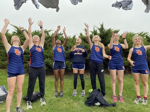 Members of the varsity girls' cross country team celebrate their victory.